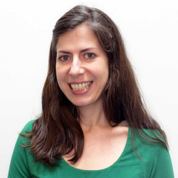 Staff photo of Vicky Ludas Orlofsky, in green, smiling at the camera